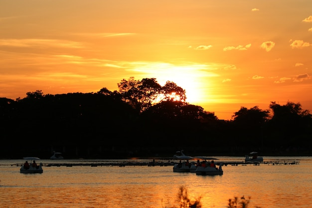 Landscape beautiful sunset in the park with silhouette people relaxing on boat