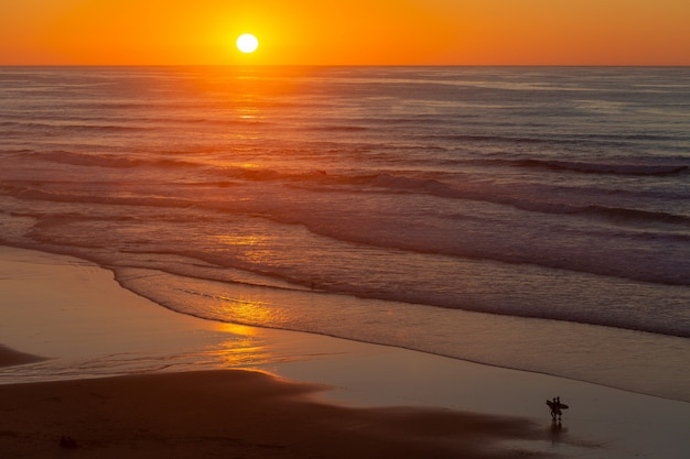 Landscape of a beautiful sunset reflecting on sea from the beach in portugal, algarve