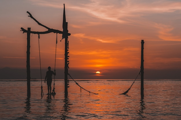 Landscape of the best sunset in gili island in famous swing in indonesia with, red sky