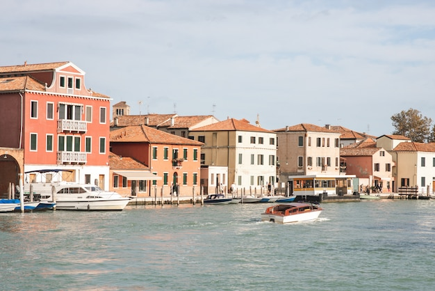 The landscape of the boat sea and the architecture of the island of murano, venice. tourism in the islands of venice.