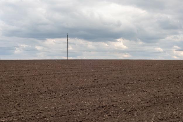 Пейзаж изменение климата поле наполовину зеленое и вспаханное на фоне облачного неба.