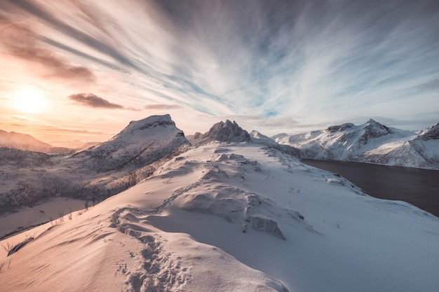 Landscape of colorful snowy hill with footprint at sunrise