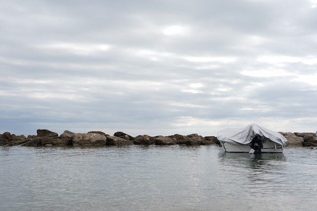 Landscape of covered boat on the sea under a cloudy sky