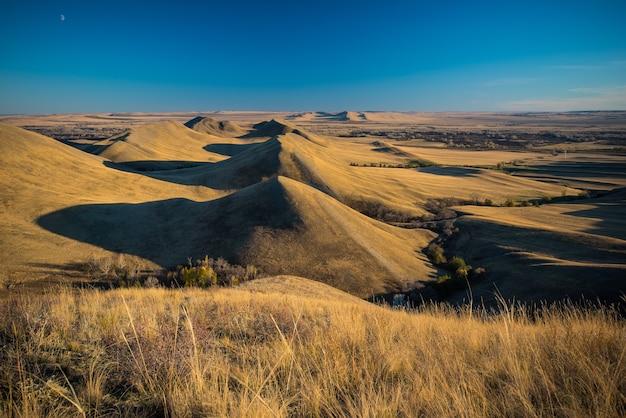 Пейзаж золотые холмы, маленькие горы на фоне голубого неба