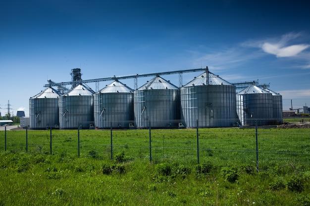 Landscape of grain elevator at field against deep blue sky