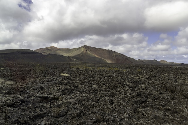 Landscape of hills under a cloudy sky in the timanfaya national park in spain