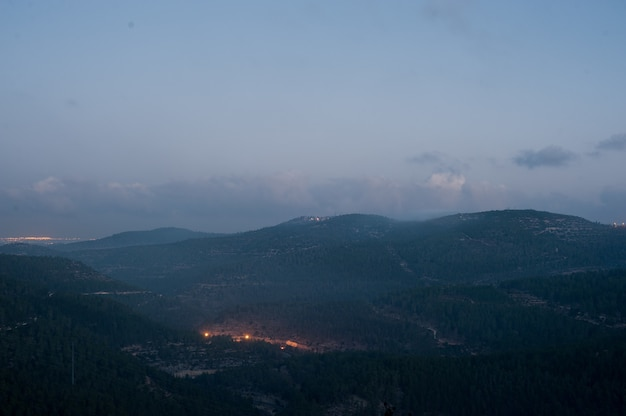 Landscape of hills covered in forests and lights under a cloudy sky during the evening