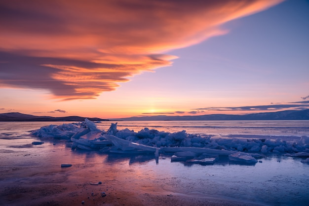 Landscape image of natural breaking ice over frozen water at dramatic sunset on lake baikal, siberia, russia.