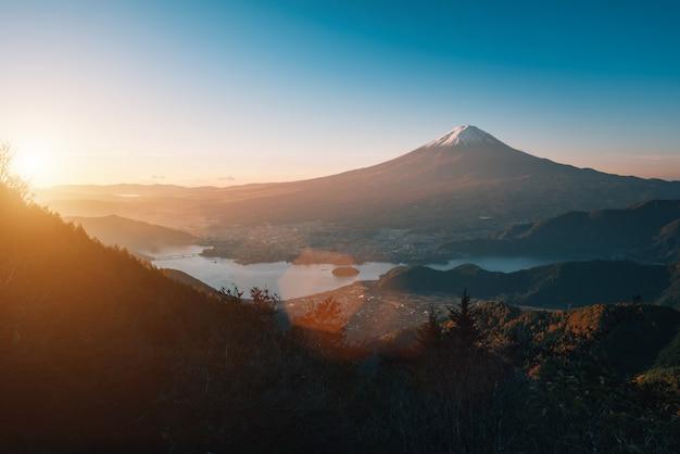 富士河口湖の日の出の秋の紅葉と河口湖の上の富士山の風景画像。