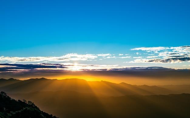 아름다운 빛의 광선이 산맥을 덮는 아침 해의 풍경 이미지와 하늘의 구름에 반사 된 빛, 자연 배경 컨셉.