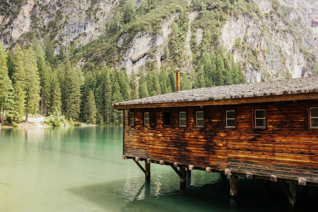 Пейзаж в lago di braies, южный тироль, доломиты, италия - деревянный дом в горах.
