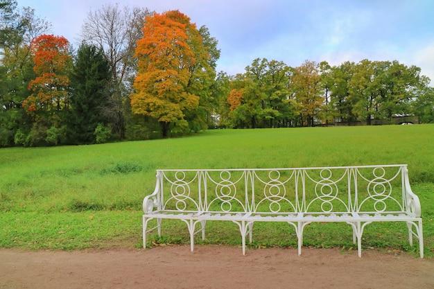 Пейзаж в парке с белой длинной скамейкой