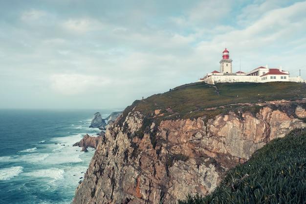 風景、ポルトガルの大西洋の海岸の急な岩の上の灯台岬ロカ