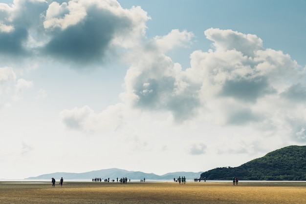 Landscape of low tide with green mountain, cloud sky with people in background at toong pronge bay in chon buri, sattahip district, thailand.
