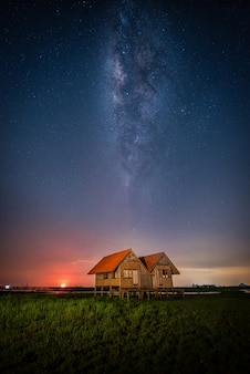 Landscape of milky way over the abandoned twin house near chalerm phra kiat road in thale noi, phatthalung, thailand