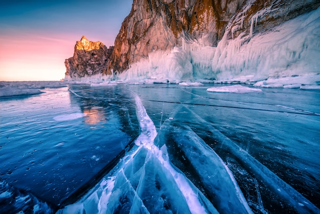 Landscape of mountain at sunset with natural breaking ice in frozen water on lake baikal, siberia, russia.