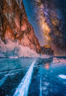 Landscape of mountain with natural breaking ice and milky way in frozen water on lake baikal, siberia, russia.