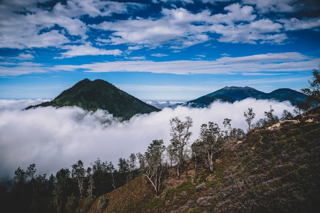 Landscape of mountains amount fog in kawah ijen volcano, java, indonesia.