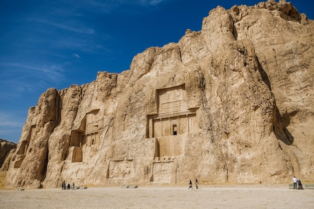 Landscape of the naqsh-e rustam shows large tombs cut high into the cliff face. iran.