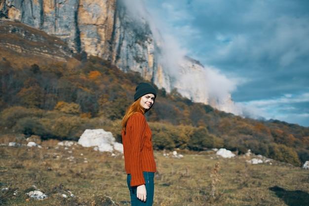 山の観光モデルでセータージャケットと帽子で旅行する風景自然の女性