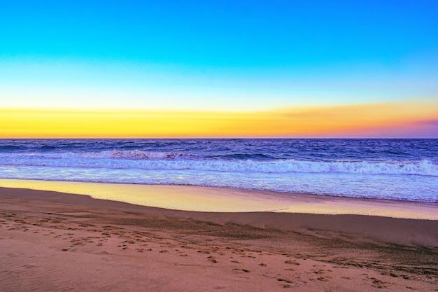 夕方のオレンジ色の日没時に海の波に囲まれたビーチの風景
