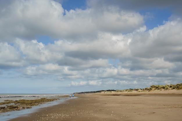 何人かの人々が歩いているビーチと白い綿の雲と広い青い空の風景