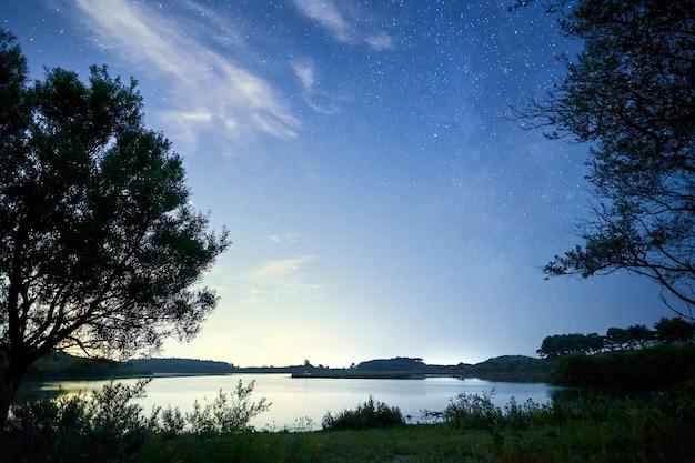 구름과 별이 있는 밤의 아름다운 호수 풍경