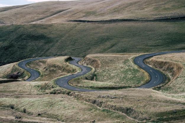 昼間は草に覆われた丘に囲まれた曲がりくねった道の風景