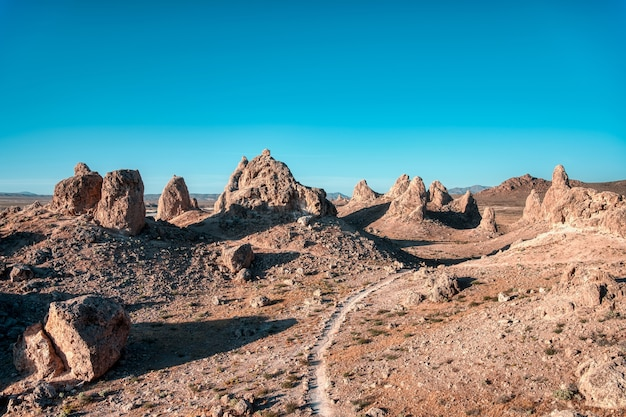 澄んだ空の下に空の道と崖のある砂漠の風景