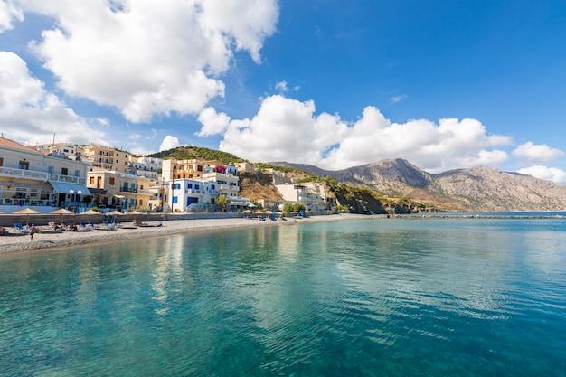 Пейзаж моря в окружении гор зданий и пляжей под голубым облачным небом в греции
