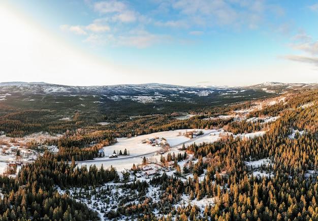 青い空と日光の下で雪に覆われた森に囲まれた村の風景