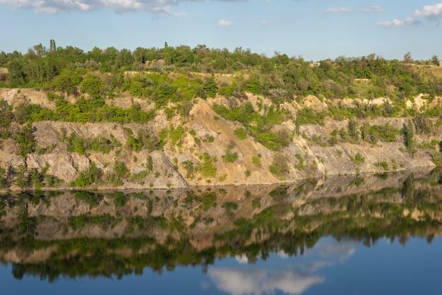 水の反射曇り空で、夏に放棄された花崗岩の採石場の風景。