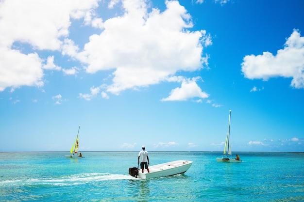 Пейзаж изумительного вида на океан. человек, ловящий рыбу на маленькой лодке