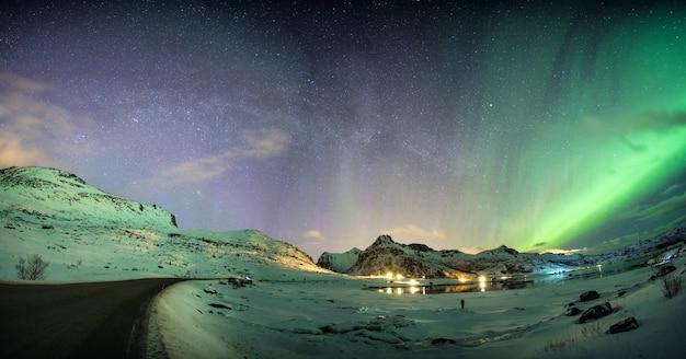 北極の海岸線の山脈に星が輝くオーロラの風景