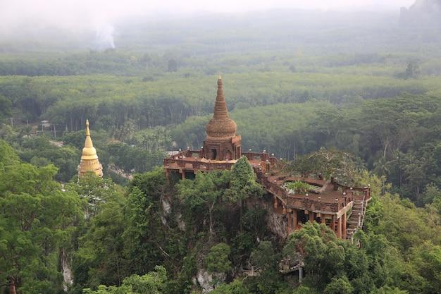 태국 남부 수랏타니 주 나 나이 루앙 사원에서 안개 낀 아침이 있는 정상 산과 나무에 탑이 있는 아름다운 일출의 풍경