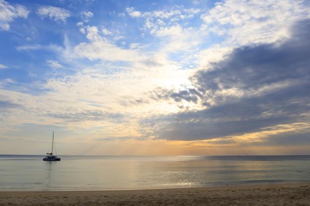 Пейзаж яркого моря и облаков с золотыми лучами солнца выходят из-за облаков с лодкой на море.
