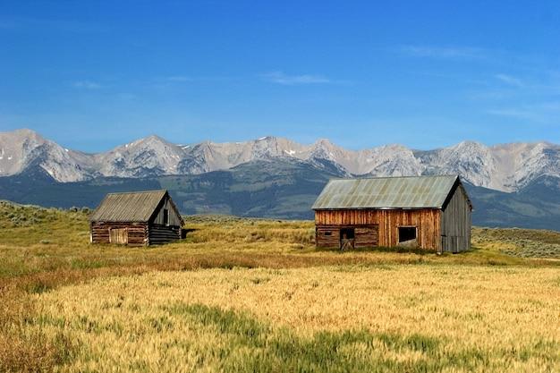 마른 초원과 montnan usa crazy mountains에있는 두 개의 오래된 목조 주택의 풍경