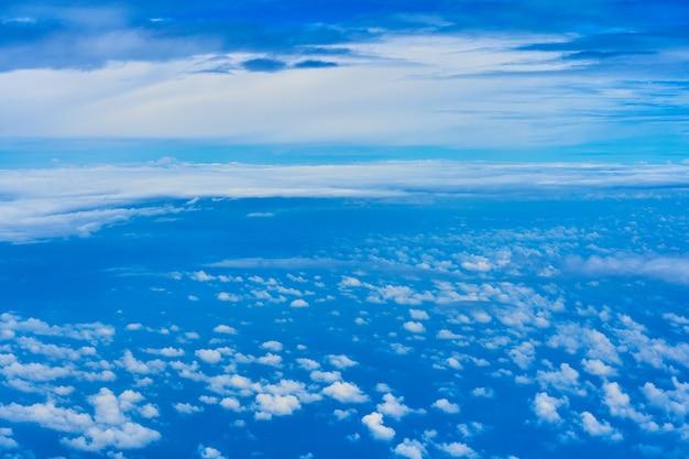 어두운 푸른 하늘에 무성한 흰 구름의 풍경. 높은 고도에서 비행기에서 봅니다.