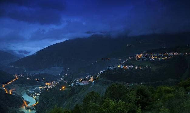 夜の曇り空の下で建物や森に覆われた丘の風景