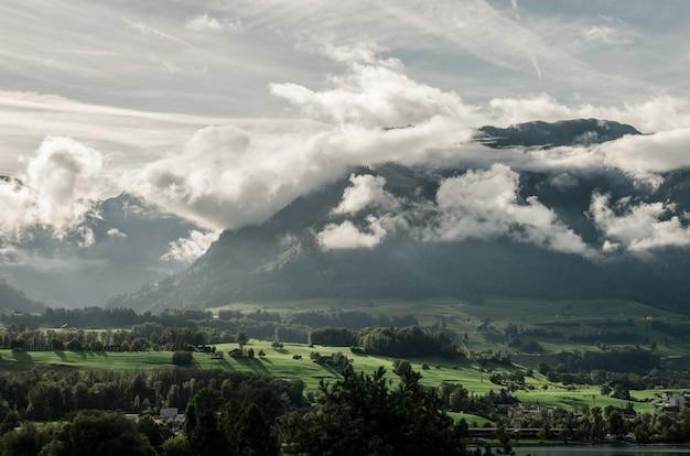 Пейзаж холмов, покрытых зеленью и туманом под солнечным светом и облачным небом