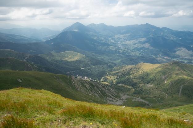 Пейзаж холмов, покрытых зеленью, со скалистыми горами под пасмурным небом на заднем плане