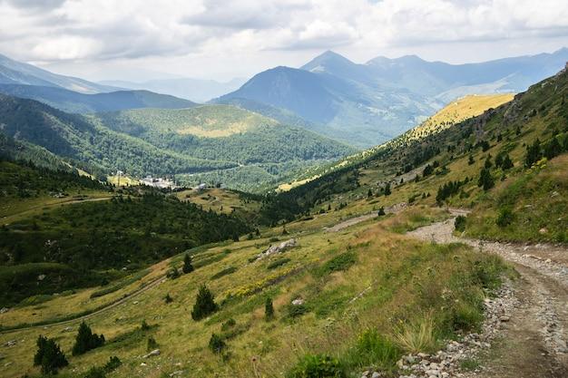 Пейзаж холмов, покрытых зеленью, со скалистыми горами
