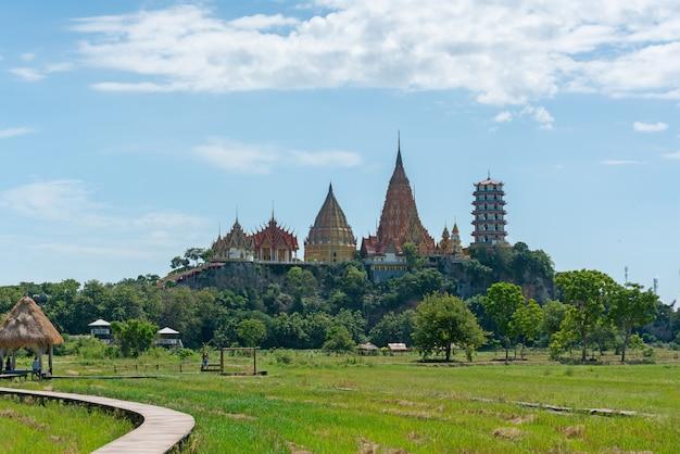 Пейзаж пышного зеленого поля и окружающих гор в храме ват тум суа (храм тигровой пещеры) в канчанабури, таиланд