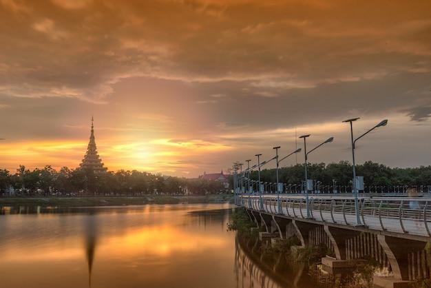 Пейзаж металлического моста и храма в закате
