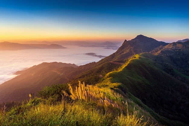 Пейзаж утреннего тумана и гор на восходе солнца.