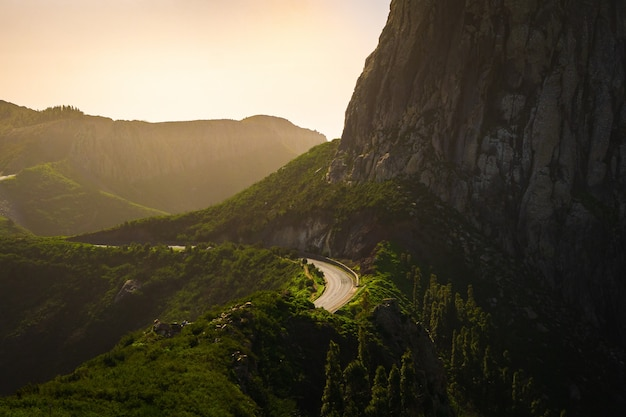 Пейзаж гор, покрытых зеленью с дорогами на них под пасмурным небом во время заката