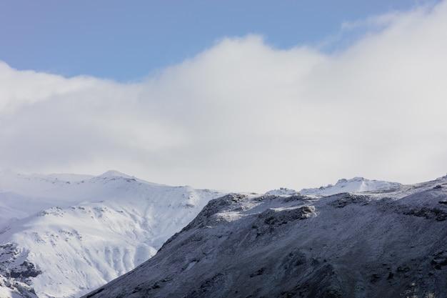 아이슬란드에서 푸른 흐린 하늘 아래 눈으로 덮여 산의 풍경