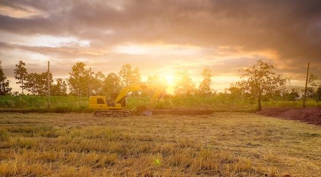 田んぼと夕焼け空の熱帯林の風景。土を掘って作業するバックホウ。冬の収穫後、田んぼの土を掘る掘削機。発掘機。発掘車両。