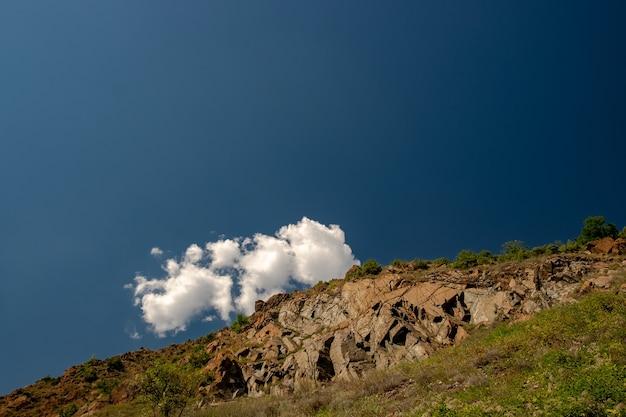 日光と青い空の下で緑に覆われた岩の風景