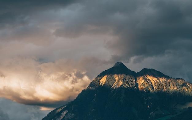 Пейзаж скал, покрытых лесами под солнечным светом и облачным небом